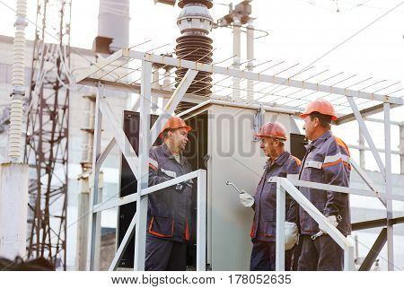 Electrical workers repair the power plant on the background of production