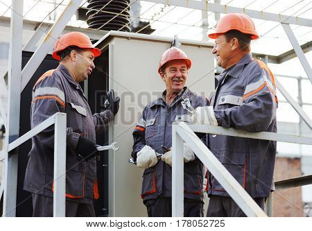 Three electrical workers discuss the problem and repair the electrical equipment