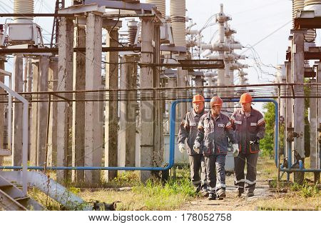 Three electric engineers on the background of a power plant in building helmets and tools in hand