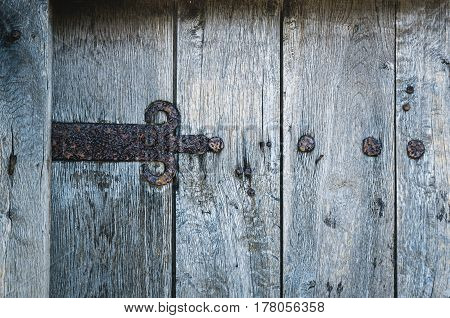 part of old wooden gate with rusted iron hinge