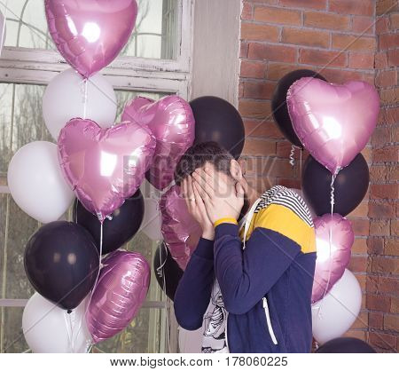 Sad or happy man covering his face .Colorful baloons on background.