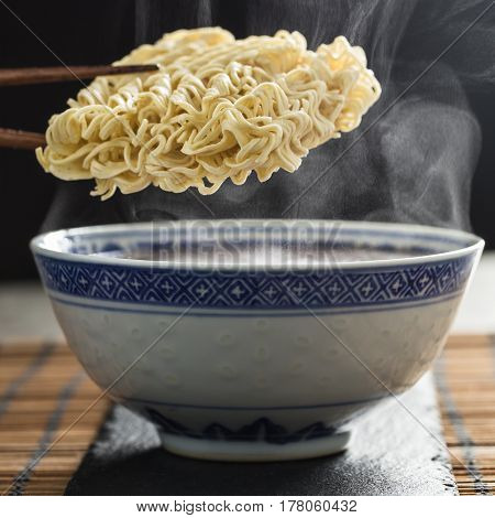 Asian instant noodles over a traditional bowl and steam.