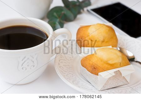 Smartphone cup with coffee pastry on plate eucalyptus branch on white table business female blogging styled image top view