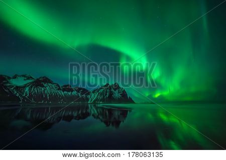 Aurora reflections on Stokksnes black beach over Vestrahorn mountains Iceland