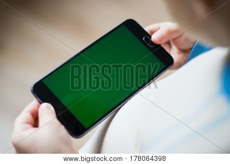 The child is holding a phone in his hand with a green screen for chroma keyer