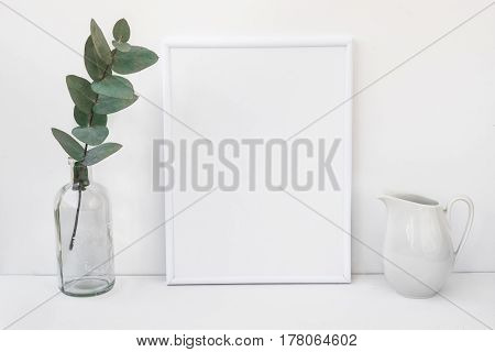 White frame mockup eucalyptus branch in glass bottle pitcher styled minimalist clean image for product marketing social media blogging