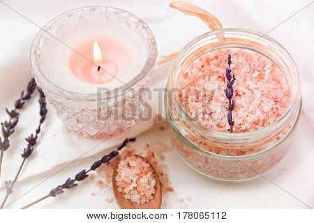 Pink Himalayan salt in glass jar burning candle wood spoon lavender on white cotton cloth styled photo for social media blogging product marketing female business