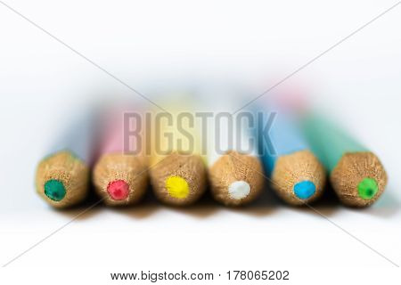 Row of colored crayons or pencils on white background macro closeup defocused abstract styled photo for product marketing social media education concept