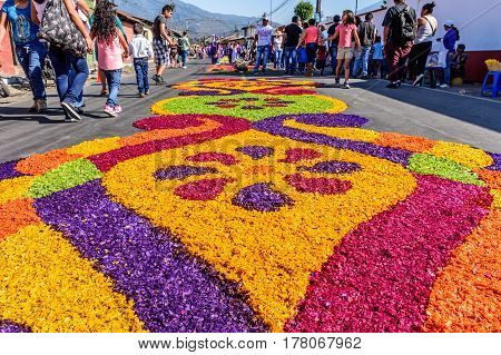 Antigua, Guatemala - March 19 2017: Locals make Lent carpets of dyed sawdust & flowers in path of religious procession in colonial town with most famous Holy Week celebrations in Latin America.