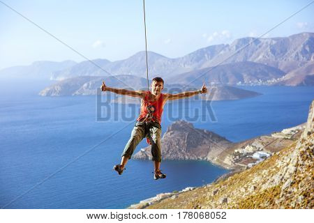 Rock climber swinging on rope and showing thumbs up sign against view of coast