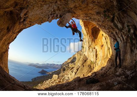 Rock climbers: one man lead climbing on ceiling in cave another belaying