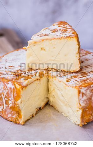 Wheel of soft camembert cheese with cut off piece on top wood cutting board clean minimalist style closeup