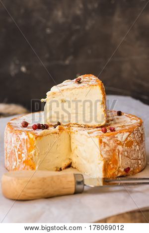 Soft French cheese on wood cutting board cut off slice fork red pepper corns rustic interior food photo