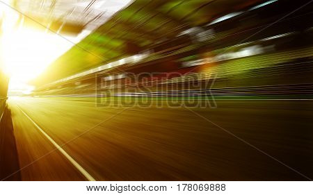 Foward motion speed lens blur racing circuit background with seated stand sunset scene .