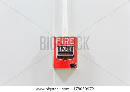 Fire alarm switch on white factory wall for warning and security system with copy space for your text.