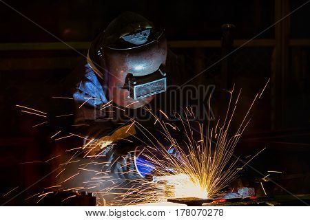 Welder is welding assembly automotive part in car factory