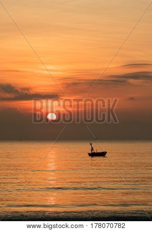 A fiery orange morning sky looking out over the south China sea in Vung Lam Bay Vietnam. With a fishing boat silhouette.