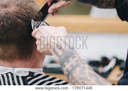 Men's Hairdressers; barbers. Barber cuts the client mac Haircut men Barbershop.