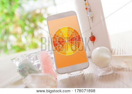 Zodiac signs and smart phone with crystal balls. Concept of modern astrology.