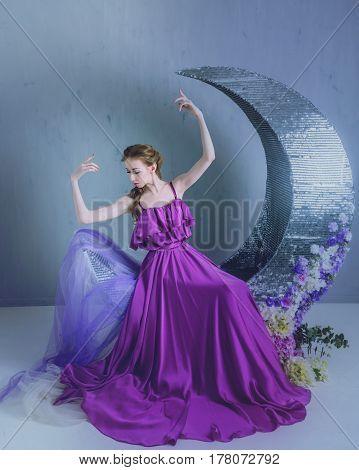 Cute girl dancer in a beautiful dress posing in the studio. Tinted photos.