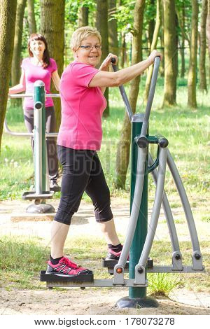 Senior And Young Woman Exercising Upper And Lower Body On Outdoor Gym, Healthy Lifestyle