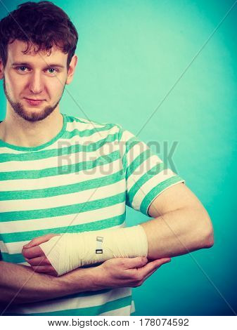 Fractures and dislocations concept. Man with hand in bandage. Helpful medication for painful palm arm of young guy.