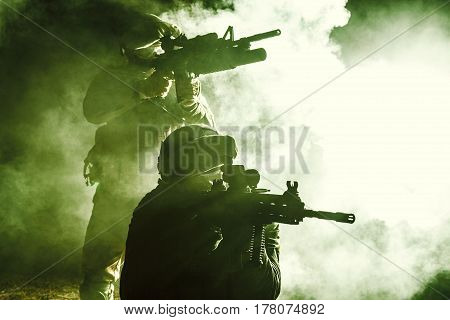 Black silhouettes of pair of soldiers in the smoke moving in battle operation. Back light, cropped, toned and colorized