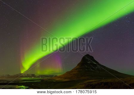 Aurora dancing with fully of stars on the sky over Kirkjufell volcano Iceland winter season landscape