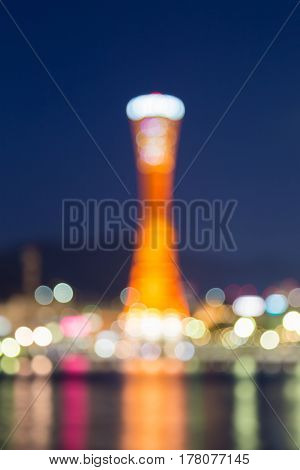 Blurred bokeh light Kobe port tower sea front with blue twilight sky abstract background