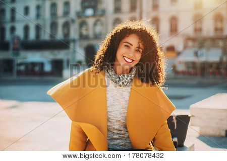 Young beautiful curly Brazilian woman with perfect smile in stylish yellow coat is sitting on a concrete bench in centre of Lisbon Portugal. Blurred facade of residential house and road in background