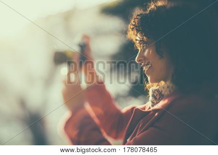 Beautiful laughing curly Brazilian woman in red coat is shooting on vintage camera true tilt shift portrait of adult white smiling lady on sunny evening using retro photo camera