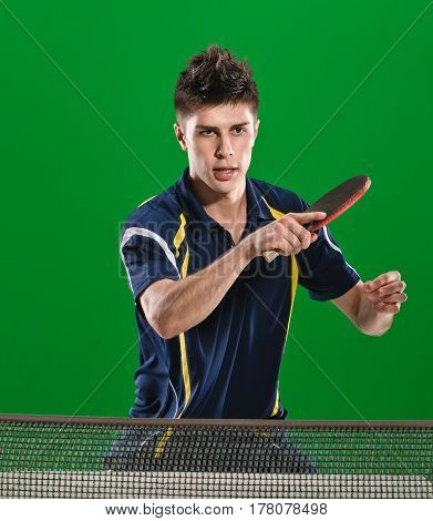Young male athlete playing table tennis on green chromakey background