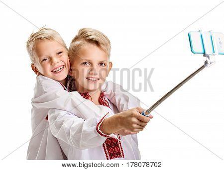 Laughing happy boys wearing vyshyvanka making selfie on monopod