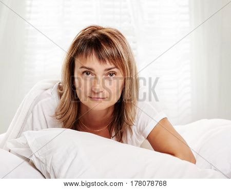 happy middle aged woman on white bed