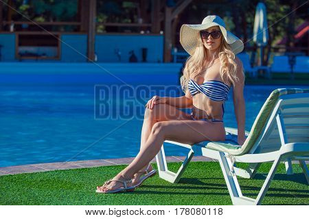 Beautiful young girl is sitting on the chaise-longue with pleasure near a swimming pool. She is wearing beautiful swimsuit, sunglasses and a hat.