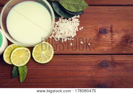 beauty, spa, body care, natural cosmetics and wellness concept - close up of citrus body lotion in glass bowl and sea salt with limes on wooden table