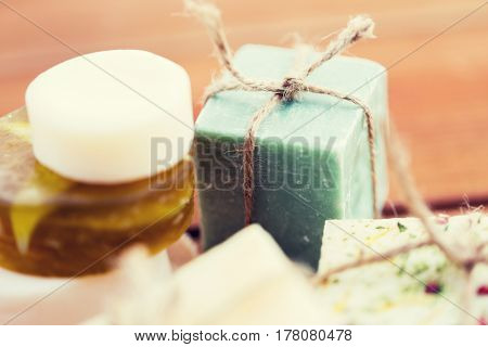 beauty, spa, body care, bath and natural cosmetics concept - close up of handmade soap bars on wooden table