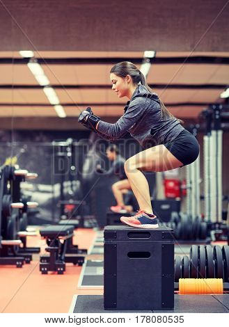 fitness, sport, exercising and people concept - woman doing squats on pnatfom in gym