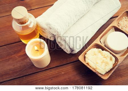 beauty, spa, body care, natural cosmetics and wellness concept - close up of soap with candle and bath towels on wooden table