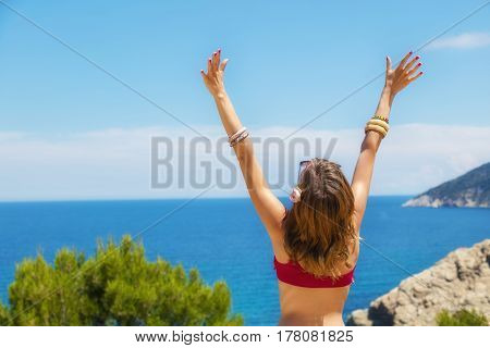 Girl enjoying outdoors with arms wide open and ocean / sea background.