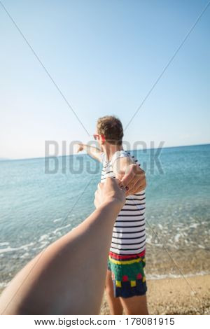 Boyfriend pulling her girl and showing to the sea / ocean. Focus is on the hands.