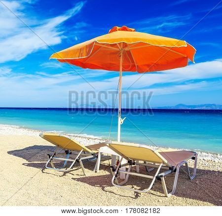 deck chairs and umbrella on a background of sea and pebbles