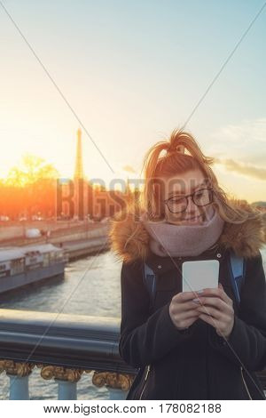 Cute girl using cellphone with Paris background.