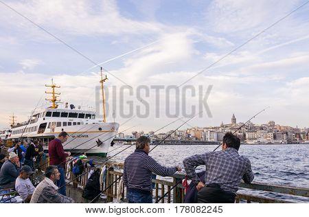 ISTANBUL, TURKEY - NOVEMBER 19, 2014: Turkish fishermen fishing on Iskele Yolu in Eminonu district in Istanbul Turkey with view over Bosporus Galata Tower and Galata Bridge