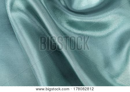 Silk background texture of green ribbed shiny fabric close up