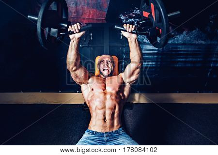 The powerfull athlete doing exercises on pectoral muscles