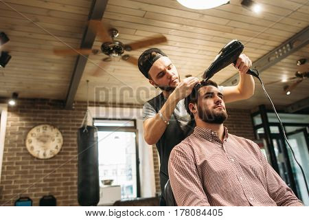 Stylist drying clients hair at salon free space. Confident businessman making hairdo. Beauty, style, modern life concept. Barbershop background