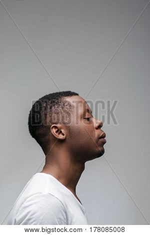 Concentrated african guy with closed eyes on grey background with free space. Getting new ideas, deep concentration, yoga, meditation. Profile view.