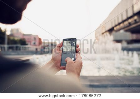 Ukraine, Kharkiv - 10 August, 2016: Pokemon Go playing game on mobile phone. Over the shoulder view with blurred background closeup. Catch a Pokemon in real world.