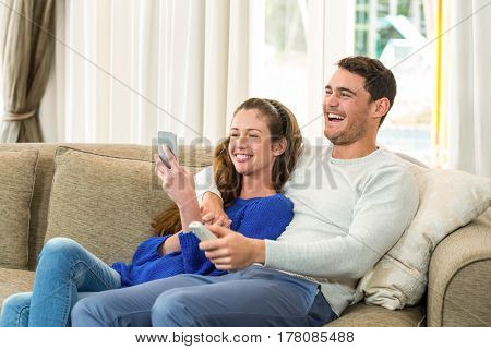 Young couple sitting on sofa and mobile phone in living room
